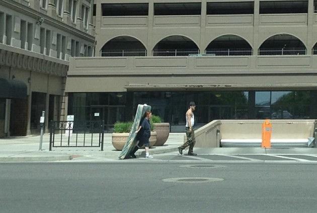 girl carrying mattress